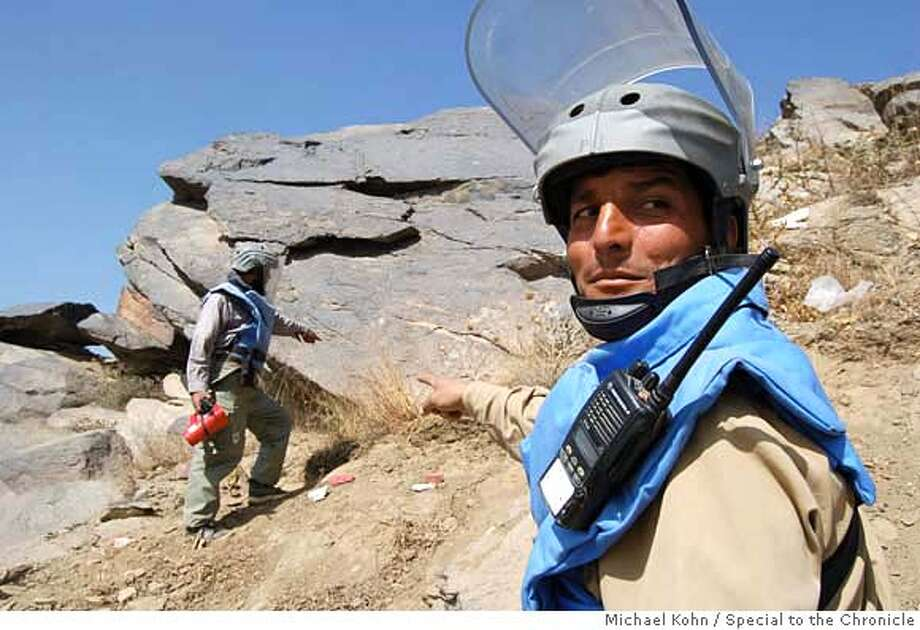 Mohammed Mahfooz (right) and Abdul Kahel spot a deadly landmine on the side of TV Mountain in Kabul. MICHAEL KOHN/SPECIAL TO THE CHRONICLE NO MAGS, , NO TV Photo: Michael Kohn