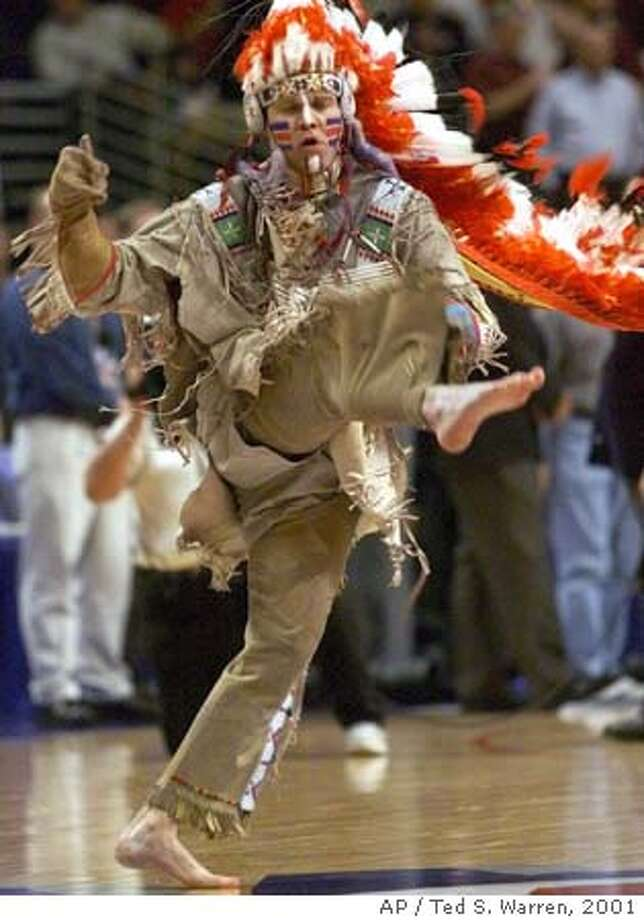 """** FILE ** Chief Illiniwek, the mascot of the University of Illinois """"Fighting Illini,"""" performs during the halftime break of a Big Ten tourney game in Chicago on March 10, 2001. (AP Photo/Ted S. Warren) EDS: A MARCH 10, 2001 FILE PHOTO Photo: TED S. WARREN"""