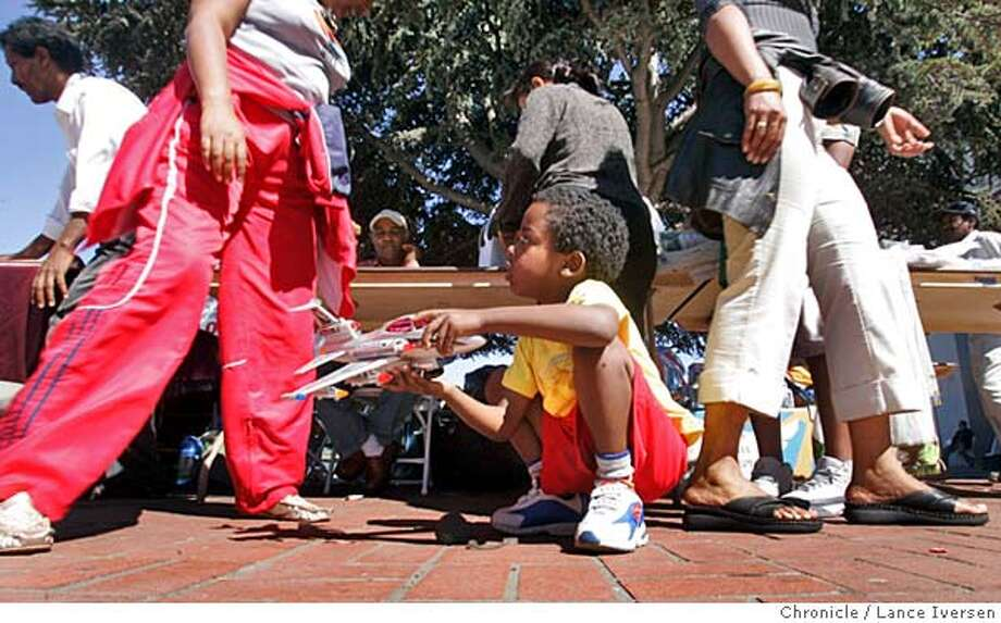 ERITREAN06_0064.jpg_  Northern California's Eritrean community is the second largest in the United States. This weekend they are gathering for their annual celebration marking the East African struggle for independence. Dan Mussa (cq) age 5 from San Jose plays with his jet plane while his parents shop at the bazaar during their visit to Will C. Wood School in Alameda one of three locations being used to accommodate the activities. By Lance Iversen/San Francisco Chronicle MANDATORY CREDIT PHOTOG AND SAN FRANCISCO CHRONICLE. Photo: Lance Iversen