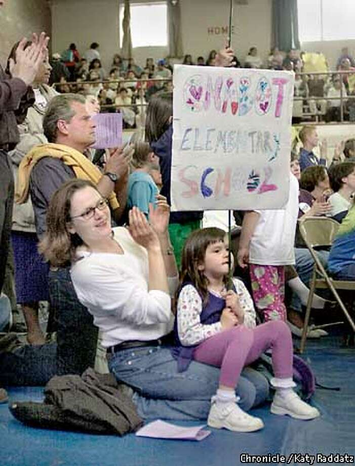 PHOTO BY KATY RADDATZ--THE CHRONICLE  Phil Meymand, and wife Alice Cannan and their daughters Leila Meymand, age 4 and Emily Meymand, age 6 are all firm believers that democracy can be won by working for it. SHOWN: Family attends a hearing about local control of schools in Oakland at St. Elizabeth's School gym. Leila sits on her mom's lap. Photo: KATY RADDATZ