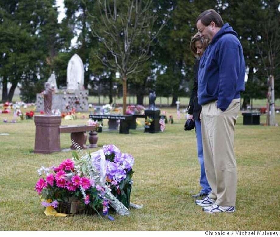 "Linda and Steve O'Connor visit the grave site of their son Kyle O""Connor on a rainy Friday morning, February 9, 2007 at St. Michael's Catholic Cemetery in Livermore, CA. (PLEASE NOTE : Linda O'Connor requested that she be photographed only from the side or back and that no close-ups of her face be published.)  Kyle O'Connor, 16, of Pleasanton died in a traffic accident on January 3, 2007 (he was a passenger and was not under the influence). The car driven by one of his friends was traveling at a high rate of speed, lost control and hit a wall by the Pleasanton DMV office.  Photo taken on 2/9/07 by Michael Maloney / San Francisco Chronicle MANDATORY CREDIT FOR PHOTOG AND SF CHRONICLE/ -MAGS OUT Photo: Michael Maloney"