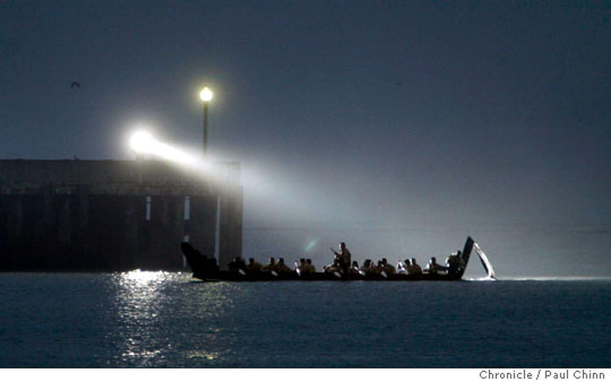 A spotlight illuminates Maori warriors as they arrive on a 52-foot-long waka (canoe) at Aquatic Park at dawn on 8/4/05 in San Francisco, Calif. to kickoff the Toi Maori art exhibit at Yerba Buena Center for the Arts. They were met by members of the Ohlone and other coastal tribes of California in a traditional welcoming ceremony. PAUL CHINN/The Chronicle
