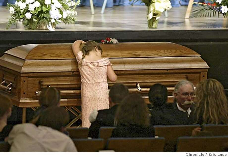 "Six-year-old Gabrielle, the daughter of San Leandro police officer Nels ""Dan"" Niemi, places a rose and then hugs her dad's casket. Photo: Eric Luse"