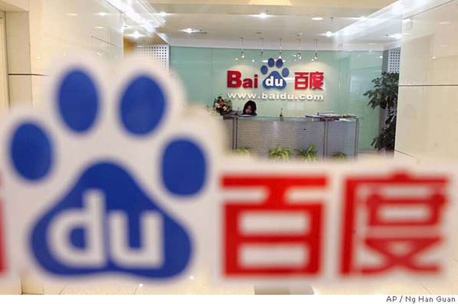 A receptionist works behind the logo for Baidu.com, a Chinese language search engine, at the company's office in Beijing Thursday, July 28, 2005. The startup hopes to become the Chinese-language equivalent of Internet search giant Google Inc., and plans an initial public offering in the United States, hoping to raise US$45 million (euro35 million). (AP Photo/Ng Han Guan) JULY 28, 2005 PHOTO Photo: NG HAN GUAN