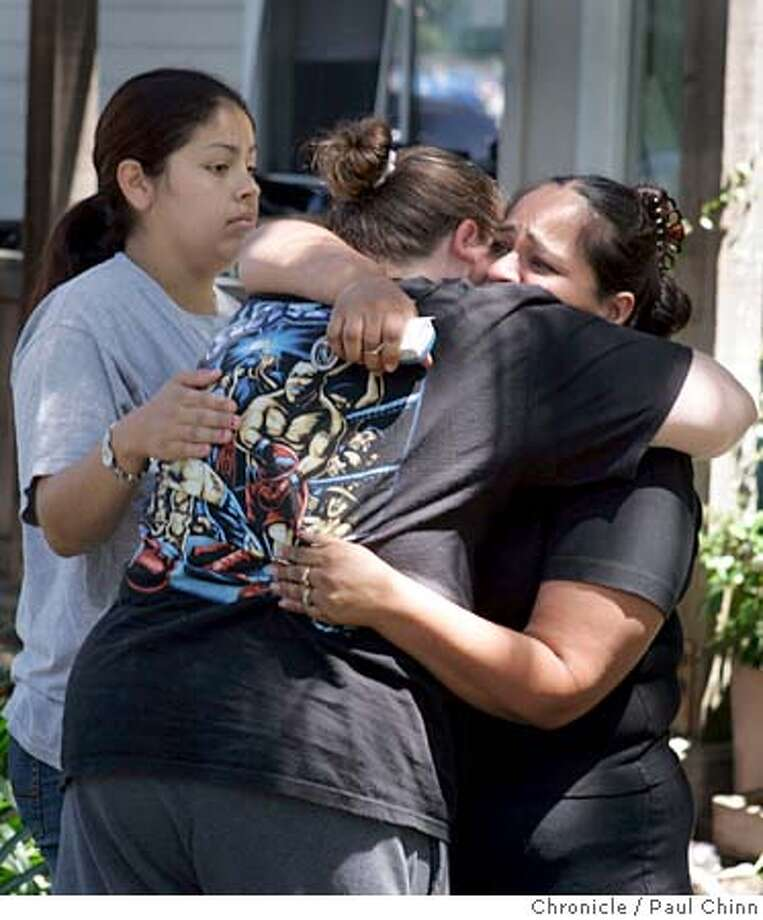 epaloalto06_061_pc.jpg  Mary Hernandez (back to camera), stepmother of 16-year-old Jorge Hernandez, is comforted by family friends Noemi Estrada (left) and Maria Macias (right) on 8/5/05 in East Palo Alto, Calif. on the morning after Jorge was shot and killed in the in their apartment complex's parking lot.  PAUL CHINN/The Chronicle MANDATORY CREDIT FOR PHOTOG AND S.F. CHRONICLE/ - MAGS OUT Photo: PAUL CHINN