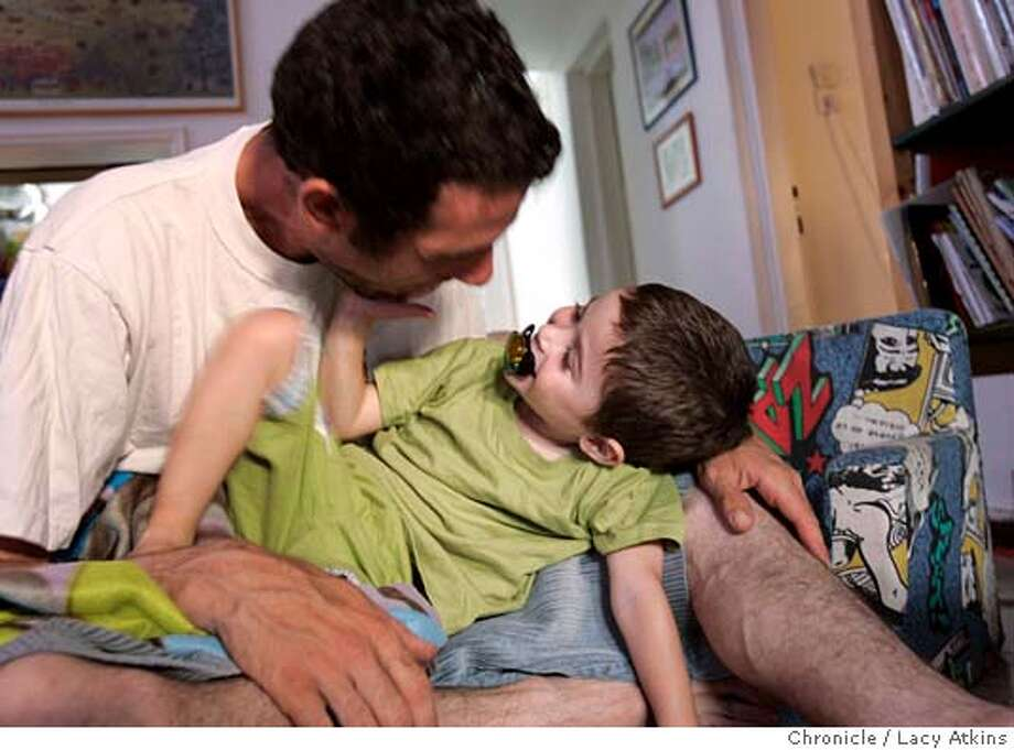 Dori Scheuer plays with his son Idan at their home in Tel Aviv, Israel, June 22,2005. Tall and rail thin, Dori Scheuer had the bearded face and the of a pacifist gardener, but his life had been irrevocably defined by being a soldier during the two Intafatas, when he was shot in the stomach by a Palestinian sniper. Scheuer married his wife Hadar in 1999, and has two children, his son Idan and daughter Mayan. Photographer Lacy Atkins Photo: LACY ATKINS