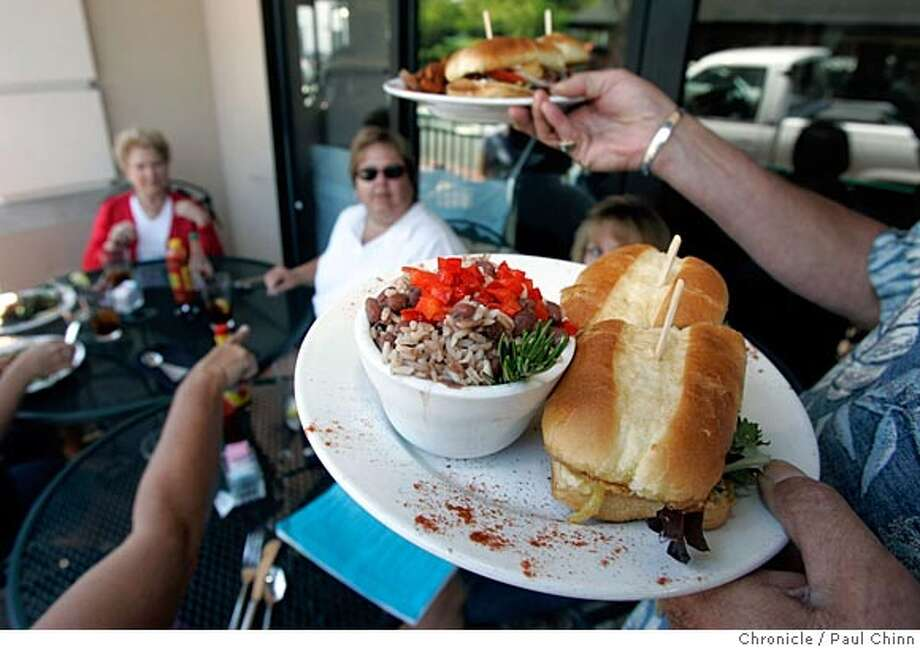 Owner Rick Parker serves up a Po'Boy sandwich with red beans and rice to diners visiting from Texas at La Beau's Louisiana Kitchen cajun restaurant on 7/30/05 in Martinez, Calif.  PAUL CHINN/The Chronicle Photo: PAUL CHINN