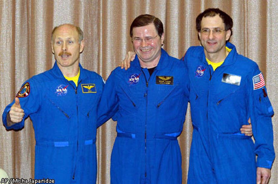 U.S. astronaut Kenneth Bowersox, Russian cosmonaut Nikolai Budarin and astronaut Donald Pettit (left to right) pose for photos. Associated Press photo by Misha Japaridze