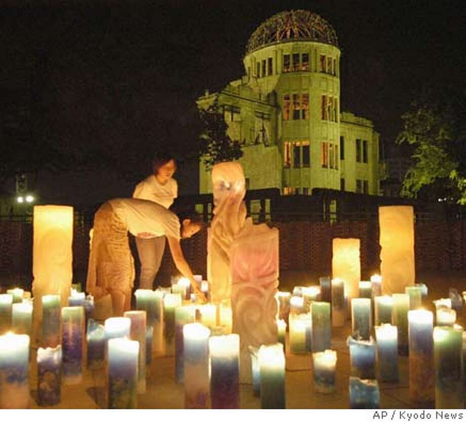 Women light candles in front of the Atomic Bomb Dome in Hiroshima, western Japan, praying for the world peace and repose of the victims of the world's first nuclear bombing early Saturday morning, Aug. 6, 2005. Marking the 60th anniversary of the atomic bomb attack, more than 55,000 people gathered Saturday in Peace Memorial Park, a sprawling, tree-covered expanse that for one day each year becomes the spiritual epicenter of the global anti-nuclear movement. (AP Photo/Kyodo News) **JAPAN OUT CREDIT MANDATORY** JAPAN OUT CREDIT MANDATORY