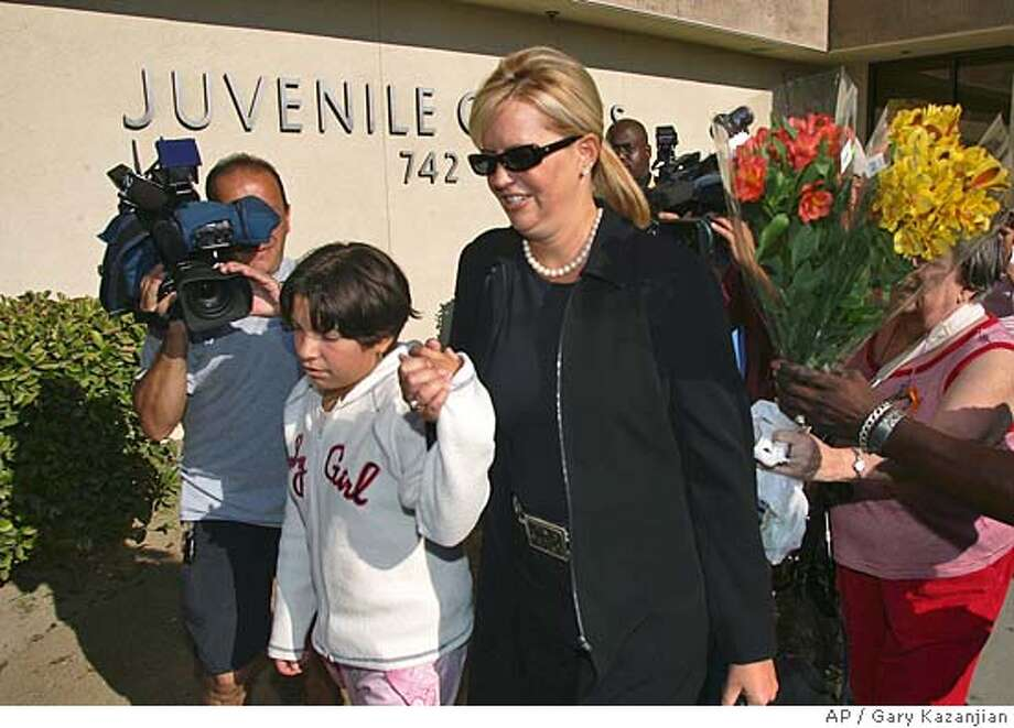 Members of the media and well wishers swarm on Maribel Cuevas, left and her attorney's assistant, Lisa Bennett, right, Wednesday, Aug. 3, 2005 in Fresno, Calif. at the juvenile court. 11-year-old Cuevas arrived to face an assault charge for throwing a rock at a boy and hitting him in the head after waterballoons were thrown at her. Cuevas spent several days in juvenile hall when police arrested her soon after the ambulance arrived.(AP Photo/Gary Kazanjian) Photo: GARY KAZANJIAN