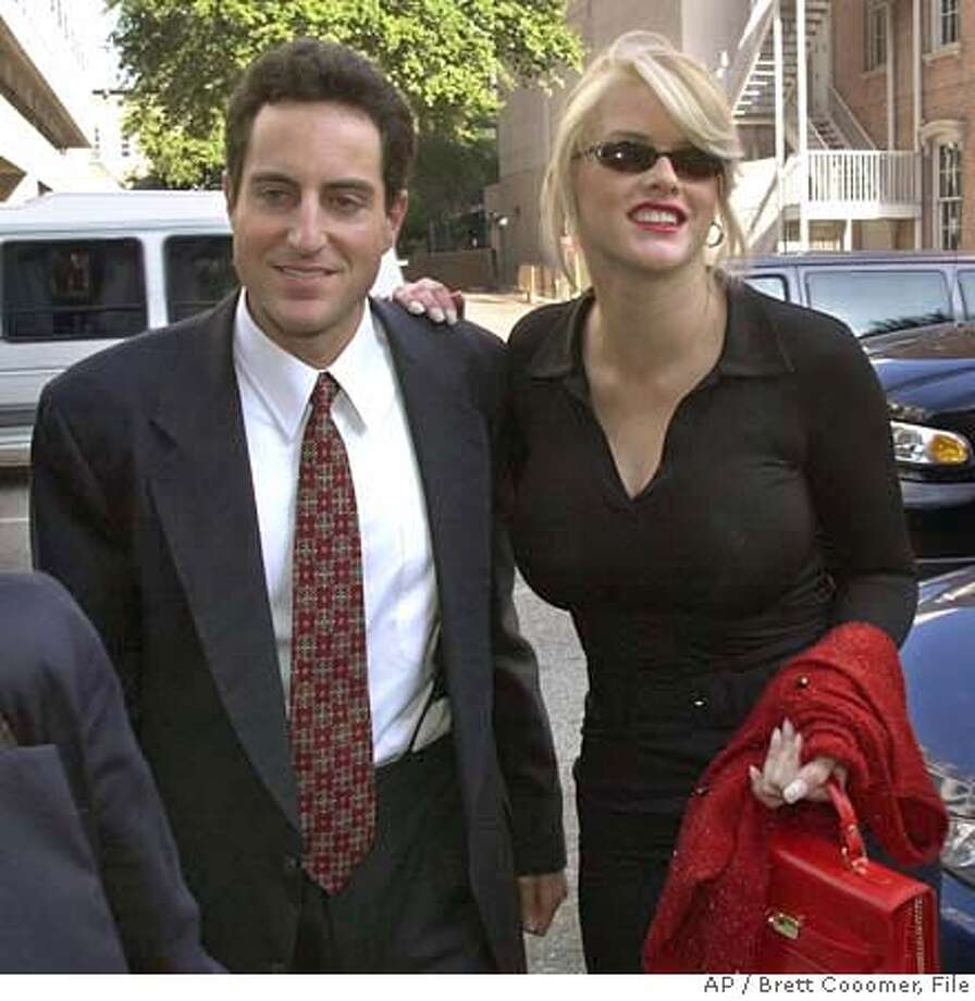 *** FILE *** Anna Nicole Smith smiles as she walks to the courthouse with Howard Stern, one of her attorneys, in this file photo from Oct. 2, 2000, in Houston. Smith, the voluptuous former Playboy centerfold who married an octogenarian billionaire and waged a legal battle for his fortune all the way to the Supreme Court, died Thursday Feb. 8, 2007. after collapsing at a hotel. She was 39. (AP Photo/Brett Cooomer-File) FILE PHOTO FROM OCT. 2, 2000 Photo: BRETT COOMER
