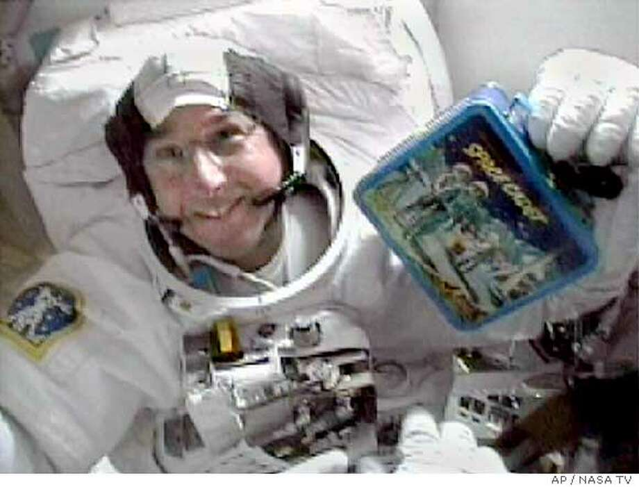 "Astronaut Steve Robinson shows his childhood lunchbox on the middeck of the Discovery in this view from television Monday, Aug. 1, 2005. Robinson brought the ""Space Cadet"" lunchbox on the spaceflight as a personal item. (AP Photo/NASA TV)"