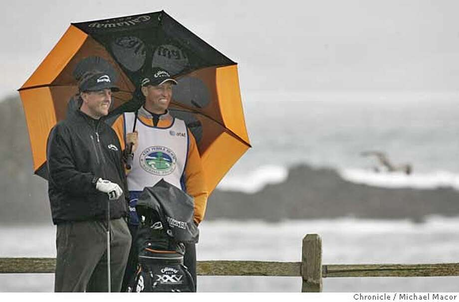 """AT&T2_259_mac.jpg Phil Mickelson along with his caddie Jim """"Bones"""" MacKay are all smiles as the wait for the tee at 18, Pebble Beach, his final hole of the day, which be birdied. Mickelson tied at 12 under fort eh tournament. Round 2 of the AT&T Pebble Beach National Pro Am Photographed in, Monterey, Ca, on 2/9/07. Photo by: Michael Macor/ San Francisco Chronicle Mandatory credit for Photographer and San Francisco Chronicle / Magazines Out Photo: Michael Macor"""