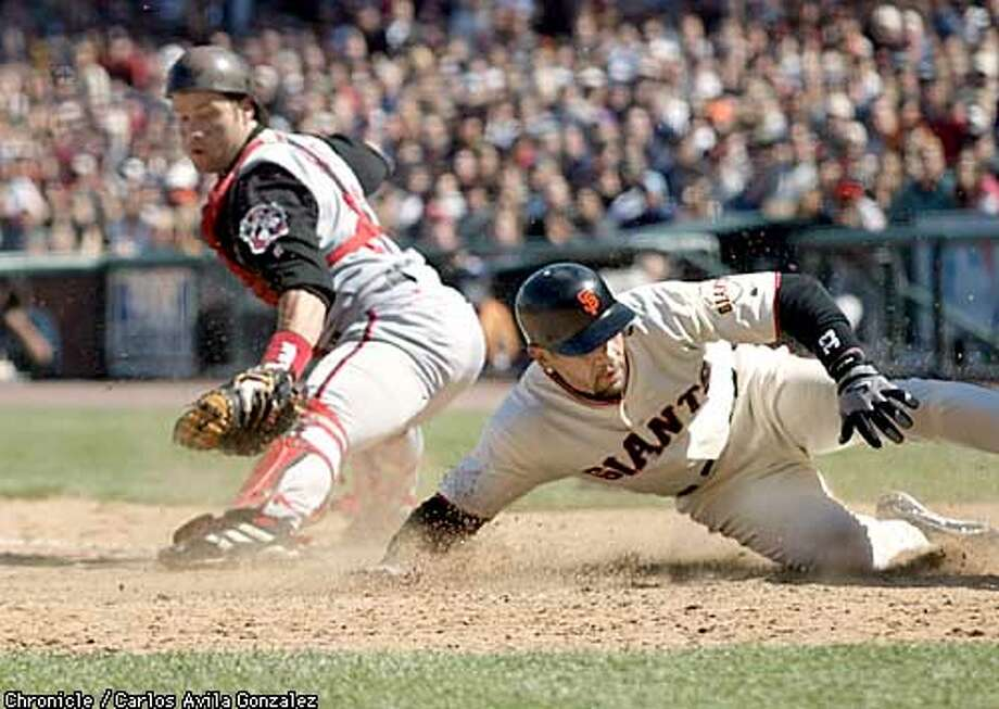 Giants's catcher, Benito Santiago, right, slides in safely past Cincinnati's catcher, Jason Larue, in the sixth inning on a Neifi Perez sacrifice fly at Pacific Bell Park on Sunday, May 4, 2003. The Giants won 6-1 against the Reds.  Event on 05/04/03 in San Francisco, CA. Photo By CARLOS AVILA GONZALEZ / The San Francisco Chronicle Photo: CARLOS AVILA GONZALEZ