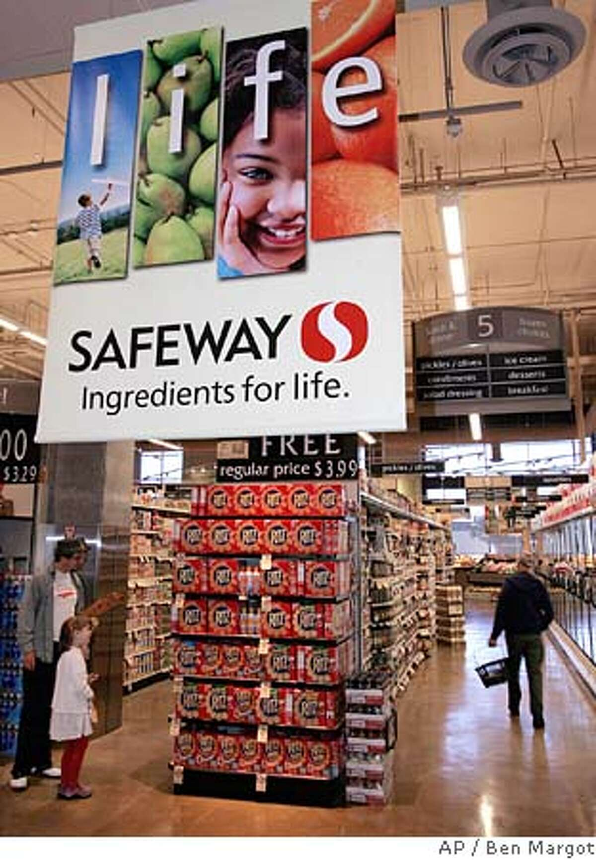 Customers shop at Safeway Monday, July 25, 2005, in San Francisco. Safeway Inc.'s second-quarter profit dropped 14 percent as higher gasoline prices and the costs of an ambitious makeover offset an uptick in sales at the big grocer. The Pleasanton-based company said Tuesday, July 26, 2005 that it earned $134 million, or 30 cents per share, during the three months ended June 18, down from $155.2 million, or 35 cents per share, at the same time last year. (AP Photo/Ben Margot)