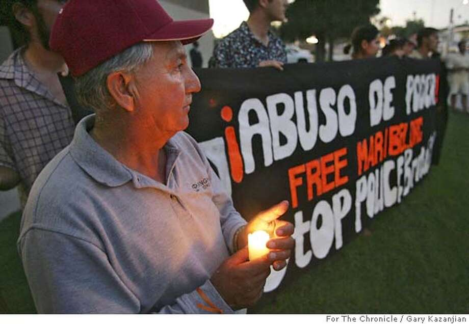 Miguel Fonseca holds a candle during a vigil in support of Cuevas with a Free sign behind him Friday, June 29, 2005 in Fresno, Calif. 11-year-old Cuevas faces a felony assault charge for throwing a rock at a boy and hitting him in the head after waterballoons were thrown at her. Cuevas spent several days in juvenile hall when police arrested her, soon after the ambulance the family had called arrived.(GARY KAZANJIAN/FOR THE CHRONICLE)