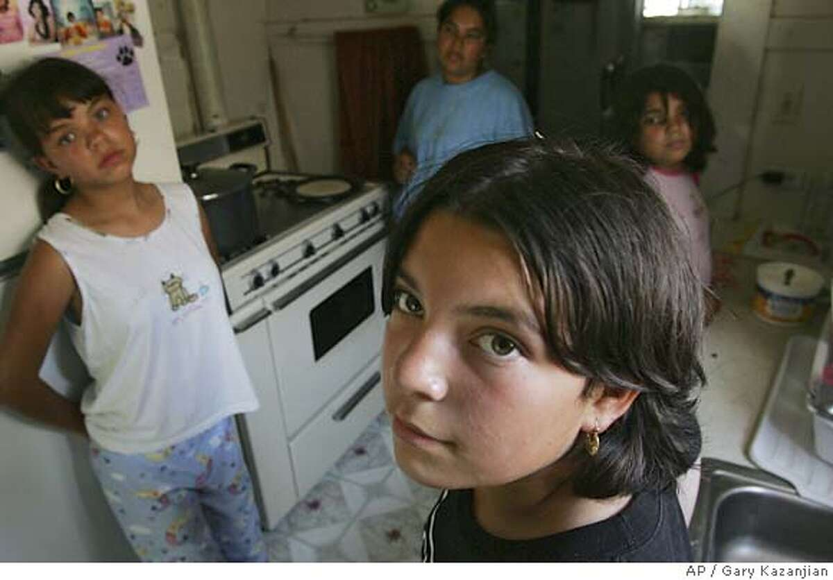 Maribel Cuevas looks on as her sister Lupita, far left, mother Guadalupe and sister Perla far right get ready for lunch Thursday, July 14, 2005 in Fresno, Calif. 11-year-old Cuevas faces a felony assault charge for throwing a rock at a boy and hitting him in the head after waterballoons were thrown at her. Cuevas spent several days in juvenile hall when police arrested her soon after the ambulance the family had called arrived.(AP Photo/Gary Kazanjian)
