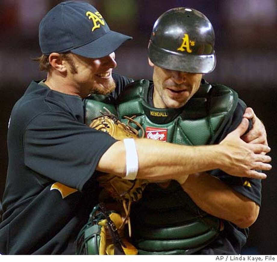 Oakland Athletics' Mark Kotsay, left, gives catcher Jason Kendall, right, a hug following the 5-4 win over the Texas Rangers, Saturday, July 23, 2005, in Arlington, Texas. (AP Photo/Linda Kaye) Photo: LINDA KAYE