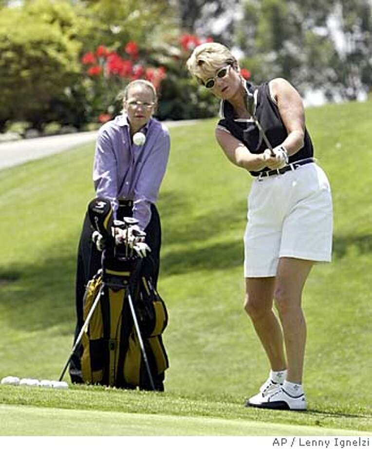 "** FILE ** Brigit Koebke pitches to a practice green at Bernardo Heights Country Club in San Diego, as her domestic partner, Kendall French, watches May 20, 2004. Deciding a case brought against the Country Club, the state's highest court said Monday that allowing the families of married members to golf gratis while charging the partners of gay members constitutes ""impermissible marital status discrimination."" The case was brought by Koebke, 48, an avid golfer who pays about $500 a month in membership fees. Koebke challenged a club policy allowing children, grandchildren and spouses of married members to play free, while her longtime partner, French, 43, could only play as a guest six times a year for up to $70 in greens fees. (AP Photo/Lenny Ignelzi) Photo: LENNY IGNELZI"