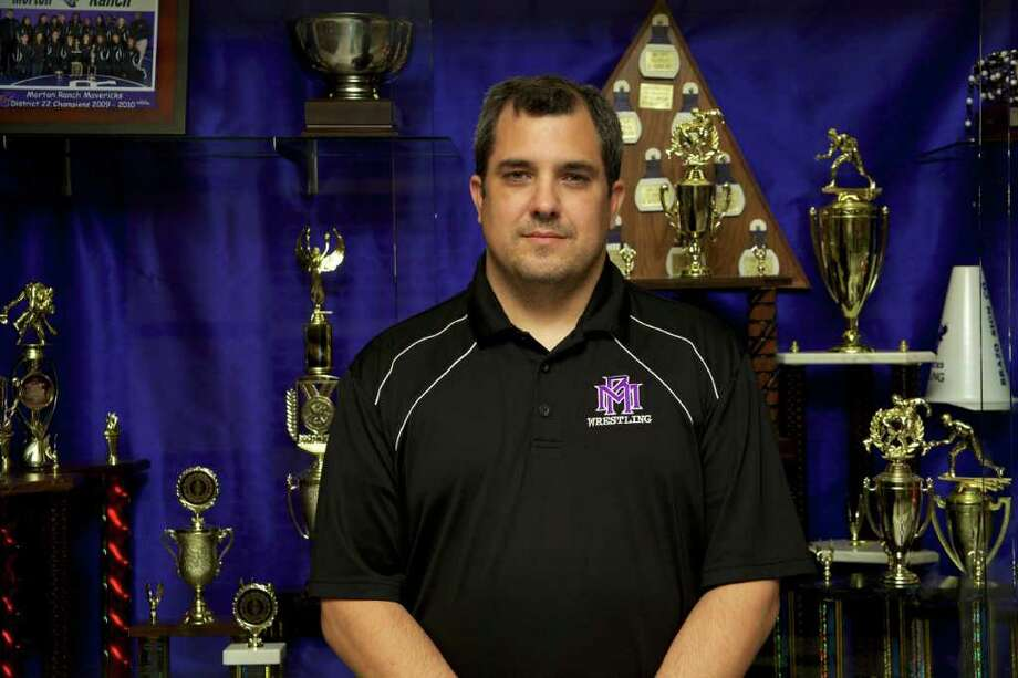 Morton Ranch High School head wrestling coach Mark Balser stands in front of the many trophies and medals that the MRHS wrestling team has been awarded. Photo by Maria-Patricia Cortez. Photo: Maria-Patricia Cortez / Freelance