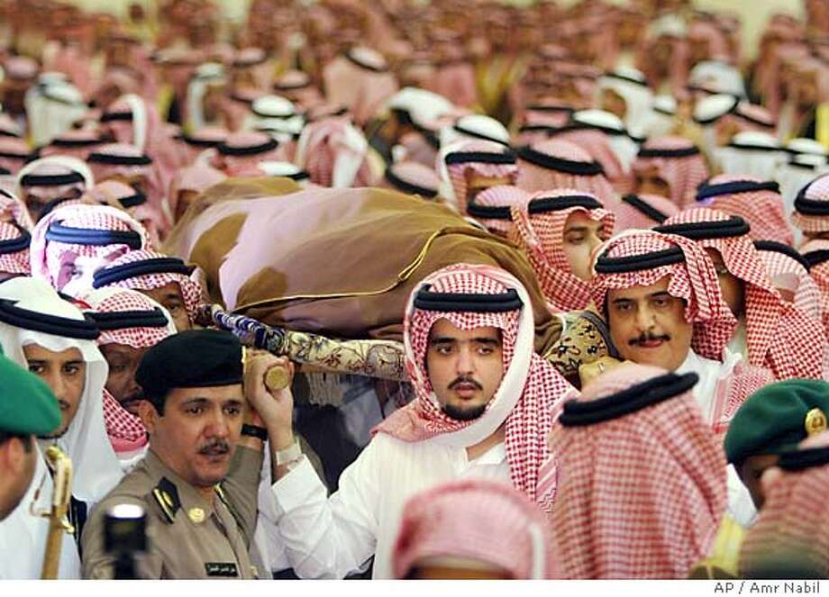 Saudi Prince Abdul Aziz Bin Fahd, a son of the late King Fahd, carries with others the shrouded body of his father before performing special prayers at Riyadh's Turk bin Abdullah mosque Tuesday Aug. 2, 2005. King Fahd died early Monday, the Saudi royal court said. He was 84. (AP Photo/Amr Nabil) Photo: AMR NABIL