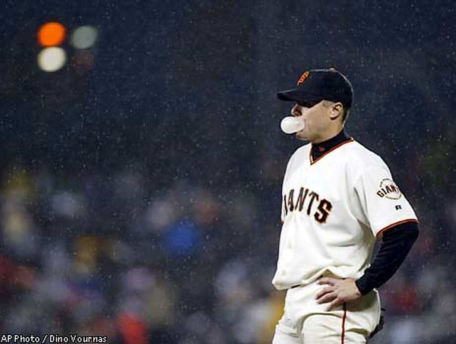 San Francisco Giants first baseman J.T. Snow blows a bubble as rain falls during the first inning against the Cincinnati Reds, Friday, May 2, 2003, in San Francisco. The start was delayed by rain, and the game was delayed in the bottom of the first. (AP Photo / Dino Vournas) Photo: DINO VOURNAS