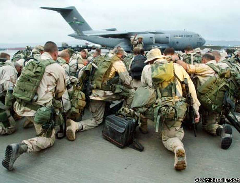 Soldiers of the 86th Contingency Response Group, one of eight groups under the 86th Airlift Wing pray on the tarmac after they arrived at U.S. Ramstein Airbase in southern Germany, early Sunday, April 27, 2003. The unit was based in northern Iraq and came back to Germany in a C17 from Kirkuk. (AP Photo/Michael Probst) Photo: MICHAEL PROBST
