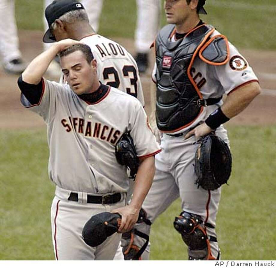 San Francisco Giants' pitcher Noah Lowry, left reacts after being pulled from the game by coach Felipe Alou, center as catcher Mike Matheny, right looks on in the sixth inning of Sunday July 31, 2005 in Milwaukee. (AP Photo/Darren Hauck) Photo: DARREN HAUCK