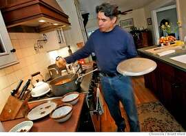 chef07113.JPG  Gabriel Fregoso squeezes out a whole head of garlic into his recipe.  Gabriel Fregoso, chef-owner of the San Rafael Mexican restaurant, Las Camelias, prepares one of his favorite family recipes at his Sebastapol home.  Fregoso prepares lamb shanks in his kitchen for a dinner with his wife, who makes pottery.  {Brant Ward/San Francisco Chronicle}1/25/07