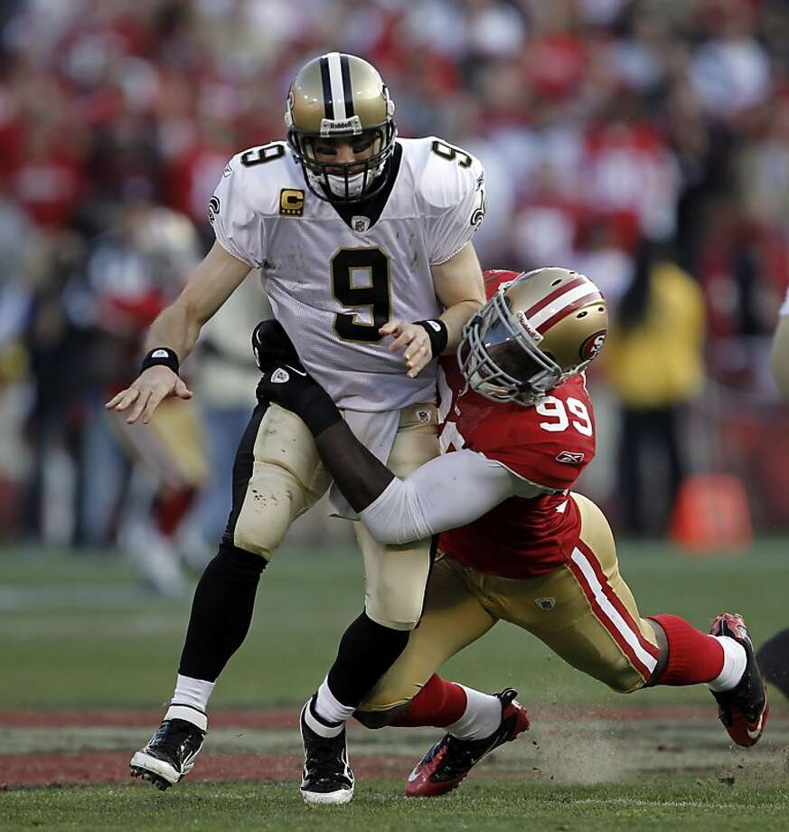 Drew Brees is hit by Aldon Smith after getting off a pass in the third quarter. The San Francisco 49ers played the New Orleans Saints in the NFC Divisional playoff game at Candlestick Park in San Francisco, Calif., on Saturday, January 14, 2012. Photo: Michael Macor, The Chronicle