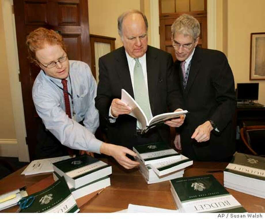 ** CORRECTS STATE REPRESENTED BY JOHN SPRATT TO D-S.C. ** House Budget Committee Chairman Rep. John Spratt, Jr., D-S.C., center, Budget Committee Staff Director Thomas Kahn, right, and Deputy Chief of Staff for the Majority Arthur Burris, look over copies of President Bush's fiscal 2008 federal budget on Capitol Hill in Washington, Monday, Feb. 4, 2007. (AP Photo/Susan Walsh) Photo: SUSAN WALSH