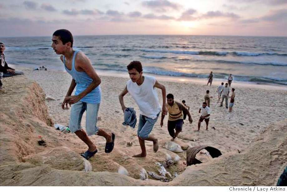 Groups of teenagers sprint up the sand drift as the sunsets along the Gaza beach, after their Hamas summercamp activities, July 10, 2005. Hamas summer camp is where the kids learn to swim, play games, march and sing intifada song. Photographer Lacy Atkins Photo: LACY ATKINS