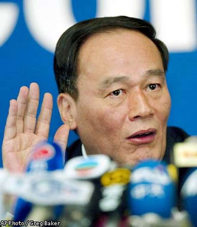 """Beijing's new Mayor Wang Qishan gestures during a news conference in Beijing, China, Wednesday, April 30, 2003. Beijing's new mayor said Wednesday the SARS outbreak """"remains severe"""" in the Chinese capital and hospitals designated to handle the disease don't have enough beds for all suspected cases.""""I think the coming week will be of critical importance in monitoring the trend of development of this disease,"""" Mayor Wang Qishan. (AP Photo / Greg Baker) Photo: GREG BAKER"""