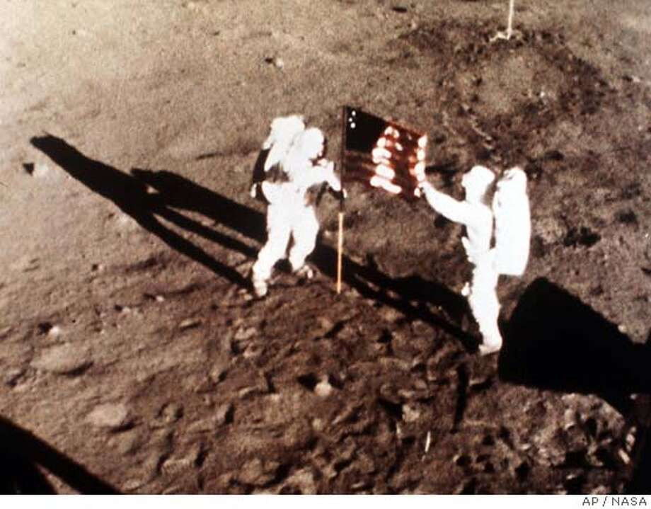"HOLD FOR RELEASE AT 3 A.M., EST, FEB. 24--FILE--Apollo 11 astronauts Neil Armstrong and Edwin E. ""Buzz"" Aldrin, the first men to land on the moon, plant the U.S. flag on the lunar surface, July 20, 1969. Photo was made by a 16mm movie camera inside the lunar module, shooting at one frame per second. The moonwalk is among the top stories of the century selected by a group of prominent journalists and scholars polled by the Newseum in Arlington, Va. (AP Photo/NASA) ALSO RAN 07/06/03  Ran on: 02-04-2007  The July 20, 1969, moon walk's fuzzy photos were taken by a 16mm movie camera.  Ran on: 02-04-2007  The July 20, 1969, moon walk's fuzzy photos were taken by a 16mm movie camera. Photo: NASA"