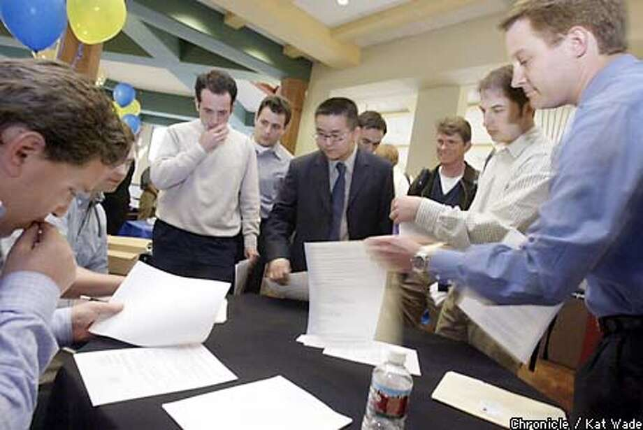 (L to R) Dave Abramowitz, the program manager of Cisco Systems, looks over resumes of MBA candidates Enrique Velez, Michael Vaynshteyn, Jeff Zhang, Manuel Ruiz, Chip Hall, Shea Heath, and David McNierney during a job fair at the U.C. Berkeley Haas School of Business Career Center on 4/22/03 in Berkeley. KAT WADE / The Chronicle Photo: KAT WADE