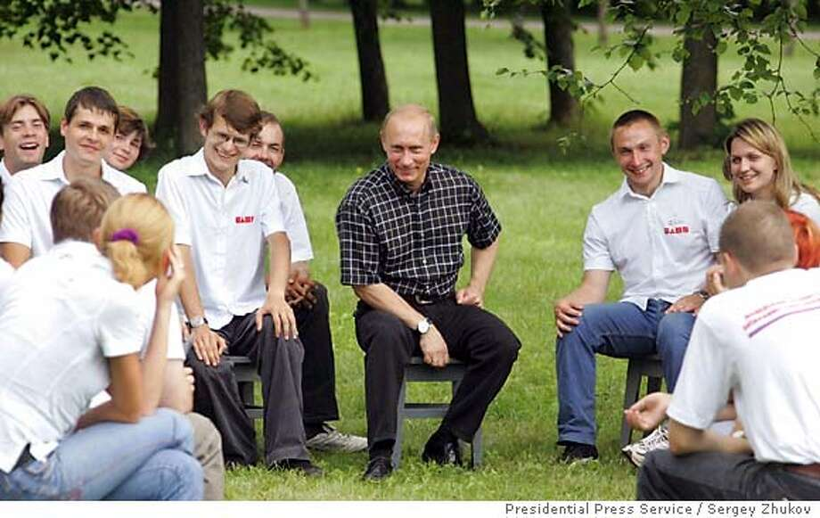 "Russian President Vladimir Putin, center, speaks with boys and girls from the Nashi youth movement during their meeting outside Moscow Tuesday, July 26, 2005. The group Nashi, which translates as ""Ours,"" calls itself a ""youth, democratic, anti-fascist movement"" and was founded on the back of another pro-Kremlin movement, Walking Together, which gained notoriety for book burnings and allegations that its members were paid for participating.(AP Photo/ITAR-TASS/Presidential Press Service, Sergey Zhukov) Photo: ITAR-TASS"