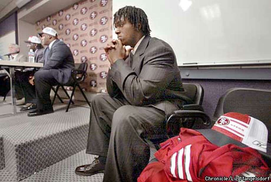Event on 4/27/03 in Santa Clara.  The 49ers 1st round draft choice Kwane Harris sits on the side, with his 49er hat and jersey next to him, as the 49er head coach Dennis Erickson(far left at table) and the 49ers 3rd draft choice Andrew Williams and their 2nd choice Anthony Adams (left to right in background) answer questions from the press at the table on the side. LIZ MANGELSDORF / The Chronicle Photo: LIZ MANGELSDORF