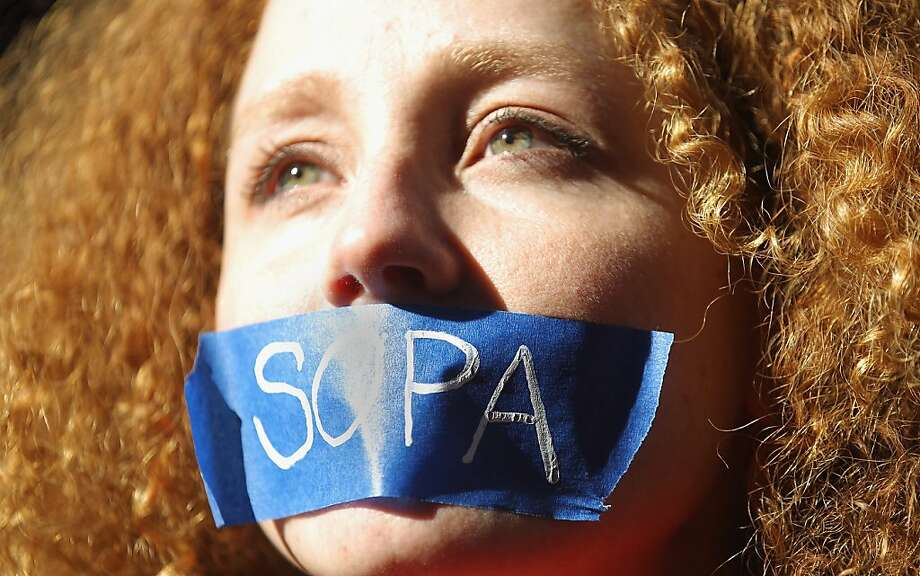 NEW YORK, NY - JANUARY 18:  Protester Nadine Wolf demonstrates against the proposed Stop Online Piracy Act (SOPA) and Protect IP Act (PIPA) outside the offices of U.S. Sen. Charles Schumer (D-NY) and U.S. Sen. Kirsten Gillibrand (D-NY) on January 18, 2012 in New York City.  The controversial legislation is aimed at preventing piracy of media but those opposed believe it will support censorship.   (Photo by Mario Tama/Getty Images) Photo: Mario Tama, Getty Images