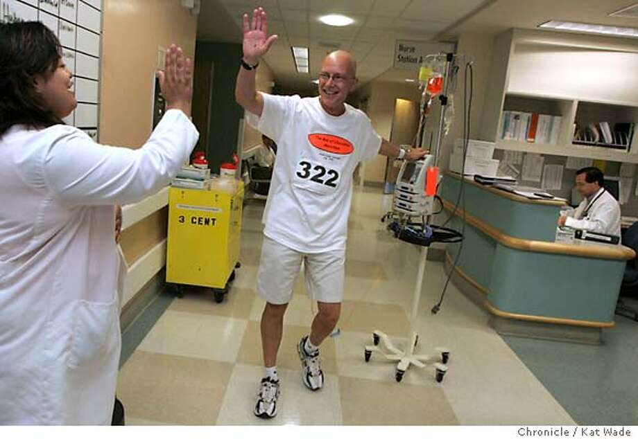 "On 7/28/05 in Walnut Creek (I HAD TO BLUR THE PATIENTS NAMES ON THE BOARD TO THE RIGHT) Emile Bets, RN gives Brian Fugere, 47, a high-five after he crossed the finish line of his 26.2 mile marathon. Brian, who was diagnose in March with a rare form of cancer called synovial sarcoma, finished the last two miles on the third day of his 26.2 mile marathon through the halls of the third floor of Kaiser Hospital while receiving his fourth round of chemotheraphy. He crosses the finish line after doing 144 laps in just over 7 hours when Brian reached his goal then continued to walk because some people pledged per mile and he said he could keep walkin Brian got out of bed one day during his third round of Chemo and started walking and before he ended had walked five miles and says he felt like ""Forrest Gump"" when he started running and couldn't stop. He couldn't stop walking and decided to do the ""Box of Chocolates Marathon"" for which he has raised $5,000.00 and has a goal of $10,000 to be donated to the Sarcoma Foundation.  Kat Wade/ The Chronicle Photo: Kat Wade"
