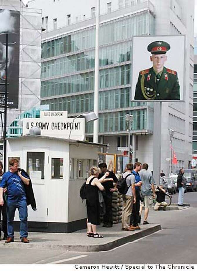 Where Checkpoint Charlie once stood, posters show a young Soviet soldier facing west and an American facing east. Photo by Cameron Hewitt, special to the Chronicle