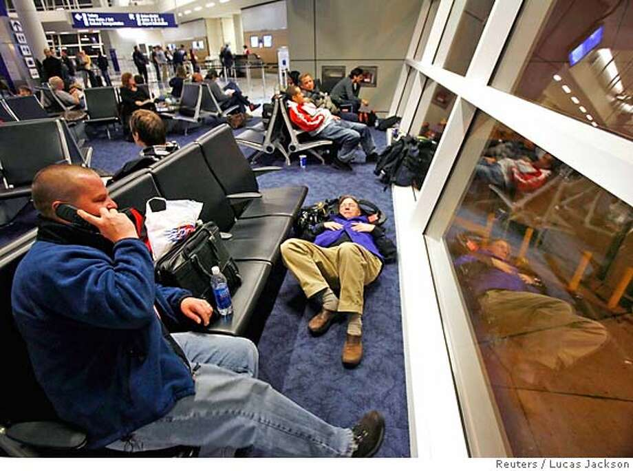 Traveller Kevin Kennedy (R) sleeps on the floor of a terminal at the Dallas/Fort Worth International Airport in Dallas, Texas January 17, 2007. Unusually cold winter weather in the area delayed and cancelled several flights out of the Dallas/Fort Worth airport leaving many passengers stranded for several hours. REUTERS/Lucas Jackson (UNITED STATES) 0 Photo: LUCAS JACKSON
