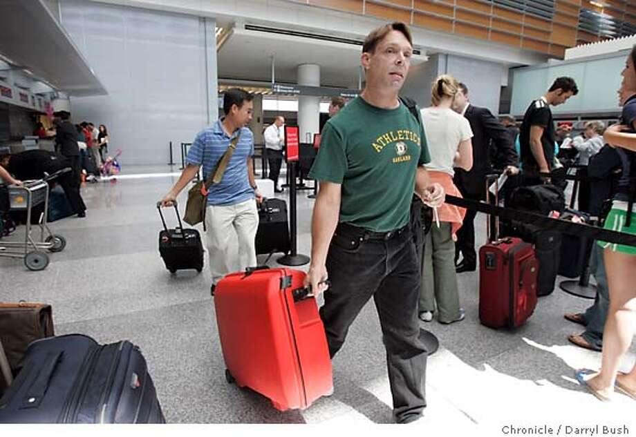 """John Heine, front right, and Andy Truong (back left), both of Concord, walk to the check-in counter for their flight to London at the Virgin Atlantic Airways ticket counter at SFO's International Terminal. Heine and Troung are taking a vacation and attending a """"gay karate tournament.""""  Event on 7/28/05 in San Francisco.  Darryl Bush / The Chronicle Photo: Darryl Bush"""