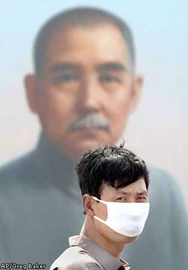 A Chinese man wears a mask to protect himself against the deadly SARS virus as he walks past a portrait of Sun Yat-sen in Beijing's Tiananmen Square Sunday April 27, 2003. Tourism has fallen off drastically since the SARS virus hit Beijing. The portrait of Sun, considered modern China's founding father for his 1911 overthrow of the Qing Dynasty, is installed each year ahead of celebrations of May Day on May 1. (AP Photo/Greg Baker) Photo: GREG BAKER