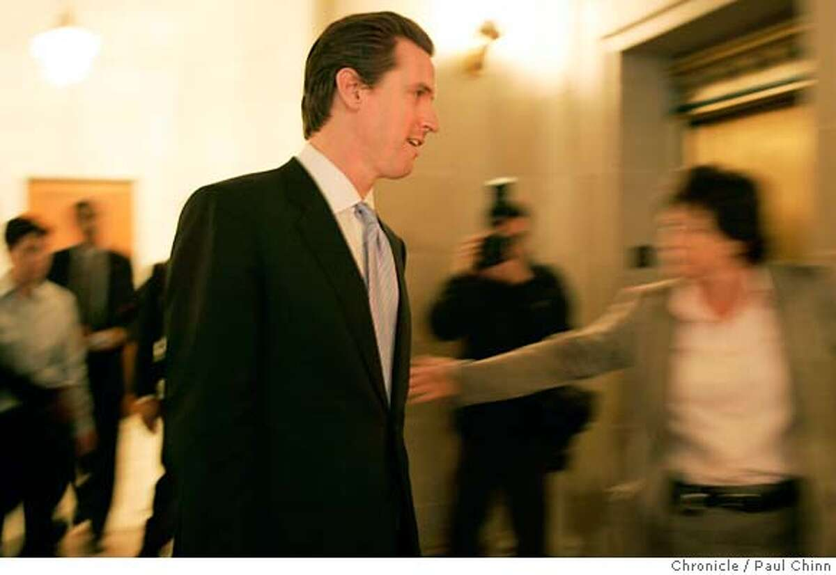 Mayor Gavin Newsom is rushed through a gauntlet of reporters on his way to attend a kick-off ceremony for Black History Month at City Hall in San Francisco, Calif. on Friday, Feb. 2, 2007 one day after acknowledging an affair with the wife of his former campaign manager Alex Tourk. PAUL CHINN/The Chronicle