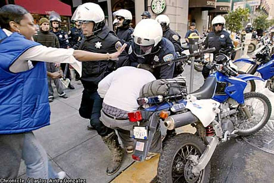 Police shove around several protesters in front of the Pacific Coast Stock Exchange in San Francisco, Ca., on Friday, March 21, 2003. No arrests were made at the scene, but protesters were admonished to remain on the sidewalk as they marched and obey traffic rules.  (BY CARLOS AVILA GONZALEZ/THE SAN FRANCISCO CHRONICLE) Photo: CARLOS AVILA GONZALEZ