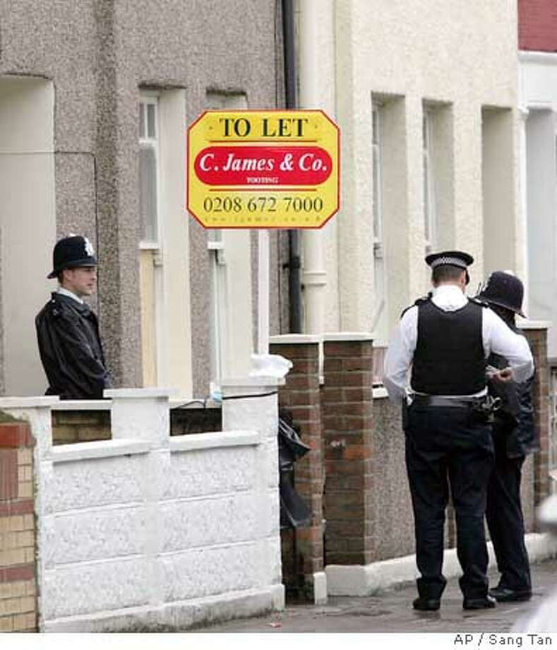 British police officers stand guard outside a house in Tooting, south London, after nine men were arrested under the Terrorism Act at two properties in the neighborhood of Tooting, in dawn raids Thursday, July 28, 2005. Britain's most senior police officer warned Thursday that terrorists responsible for last week's failed bombings on London's transport system could strike again. (AP Photo/Sang Tan). Photo: SANG TAN