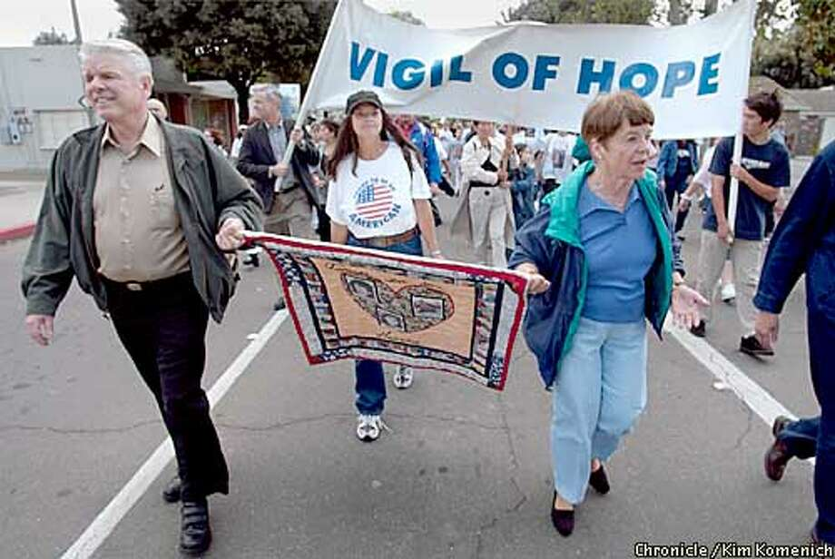 Francis (left) and Carole Carrington lead off the Vigil of Hope march in Modesto Saturday. They organized the event, which brings families of murdered and missing people whose cases are still open. They hold a quilt stitched with photos of relatives Carole and Juli Sund and their friend Silvina Peloso, who were murdered by Cary Stayner. KIM KOMENICH / The Chronicle Photo: KIM KOMENICH