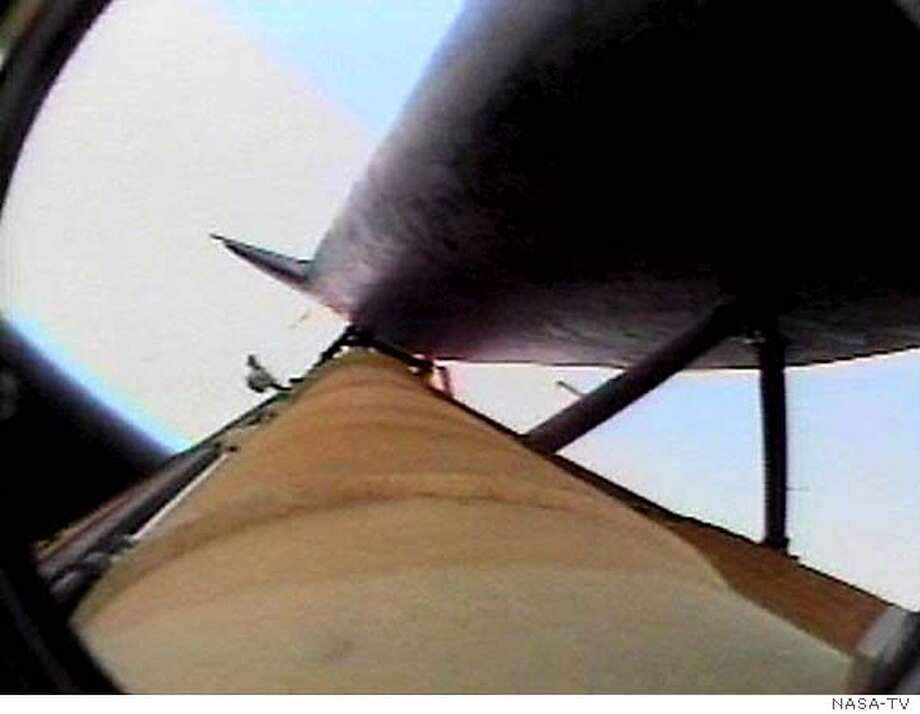 An unidentified piece of debris is visible (Centre L) near the external tank and below the bottom of the Discovery in this view from a television camera mounted on the external fuel tank after solid rocket booster separation as the spacecraft climbed to space from the Kennedy Space Center in Cape Canaveral, Florida July 26, 2005. EDITORIAL USE ONLY REUTERS/NASA TV Photo: NASA TV