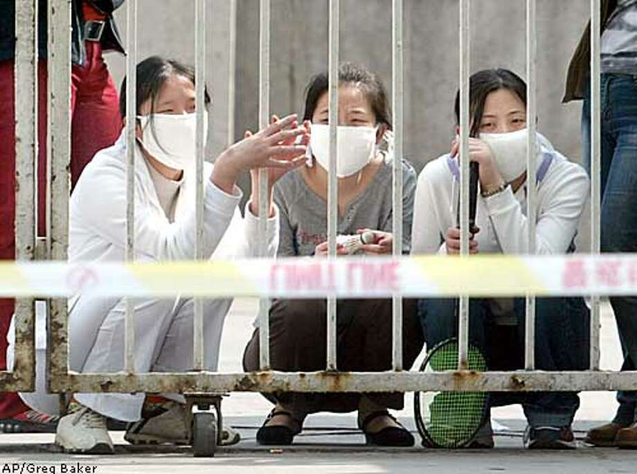 Three women crouch inside the closed gate of the People's Hospital of Peking University in Beijing Friday April 25, 2003. The hospital was sealed off Thursday amid the SARS outbreak, and many staff and patients were quarantined inside. Struggling to contain the SARS outbreak, city officials sealed off a third hospital Friday, closed some college dormitories and ordered 4,000 people who might have been exposed to the killer virus to stay at home under quarantine. (AP Photo/Greg Baker) Photo: GREG BAKER