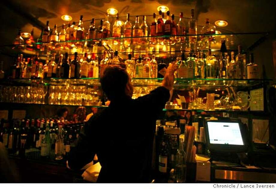 BARBITES28_2705.JPG  Bar tender Michael Deming pulls down a bottle of brandy from the extensive array offered at A Cote. College Avenue hotspot in Oakland is A Cote, an intimate restaurant that offers specialty cocktails and French/Mediterranean small plates like Italian Sausage Flatbread, Mussels with Pernod from a wood oven and Pear Gorgonzola Flatbread. Drinks include El Pepino a gin-lime cucumber, cranberry Martini type drink and The Guyana Star made with Plantation Barbados Rum, ginger and limejuice. DECEMBER 09, 2006OAKLAND.By Lance Iversen/San Francisco Chronicle Ran on: 02-01-2007  Above, left to right: A bartender pours an El Pepino, a fruity martini-type drink; Colleen Mariotti of Walnut Creek has her drink refreshed as Paul Van der Staay of San Francisco looks on; and the Italian sausage flat bread won't last long on the bar. Below: Michael Deming works the well-stocked bar at A Cote. Photo: By Lance Iversen